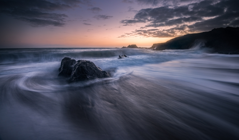 A long exposure helps capture the water receeding back towards the ocean as another wave gets ready to break. This image was created at Long Strand in Co. Cork, Ireland