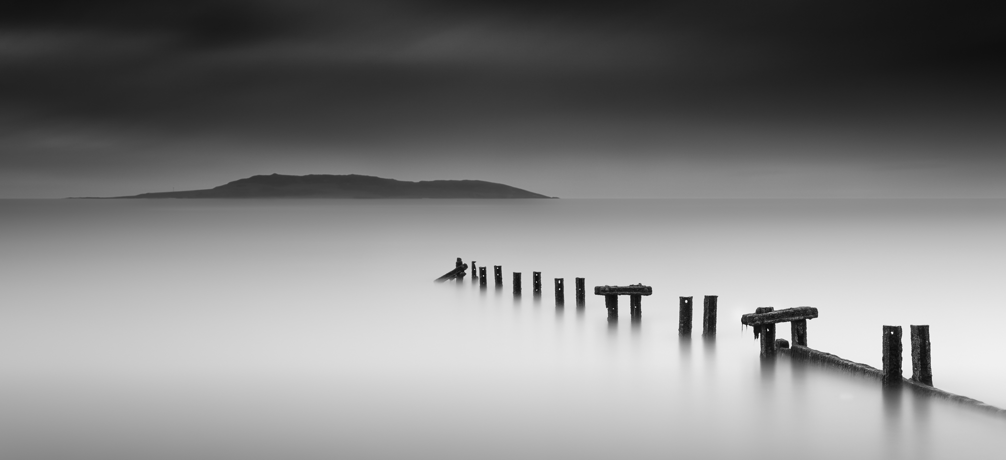 fine art long exposure seascape photo taken at malahide, dublin, ireland on an overcast day when the sunrise was not as colourful as expected